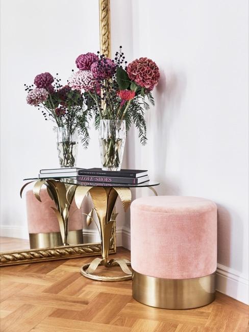 Pouf rose et table basse en métal et verre avec deux livres sur lesquels se trouve un pot de fleurs, le tout placé devant un grand miroir