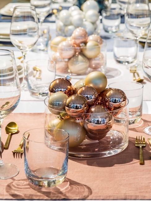 Gedekte tafel met kerstballen in glazen vaas
