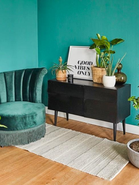 Zielony salon wraz z czarnym regałem oraz szmaragdową pufą