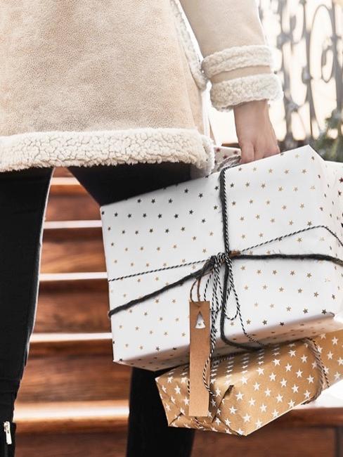 Une femme en manteau porte des paquets emballés et monte les escaliers d'une maison
