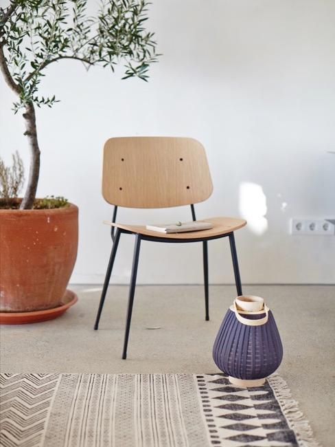 Woonkamer in wabi sabi stijl met houten stoel en grote kamerplant
