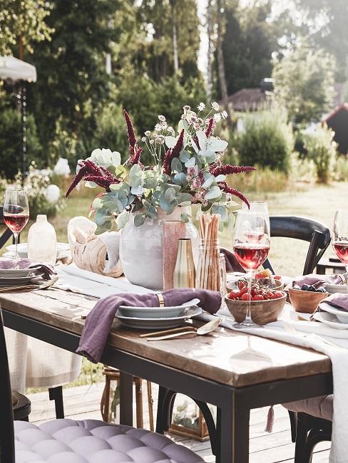 Stół w ogrodzie zastawiony talerzami, kwiatami, winem i dekoracjami
