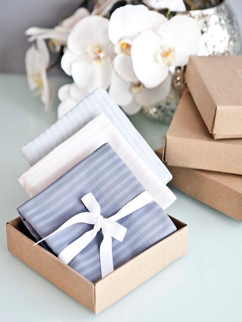 Trzy zapakowane prezenty w otwartym kartonowym pudełku z orchideami w tle