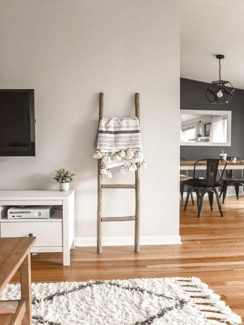 Wohnzimmer mit Teppeich, Fernseher und Lowboard, daneben ein Durchbruch zum Esszimmer