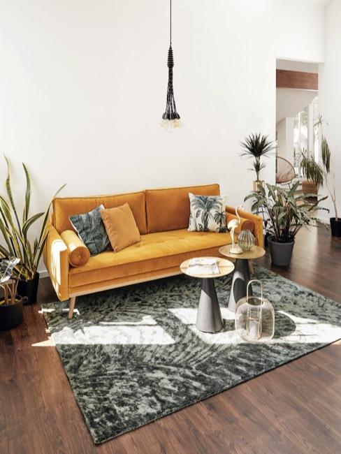 Soggiorno con divano ocra e cuscini con foglie di palma