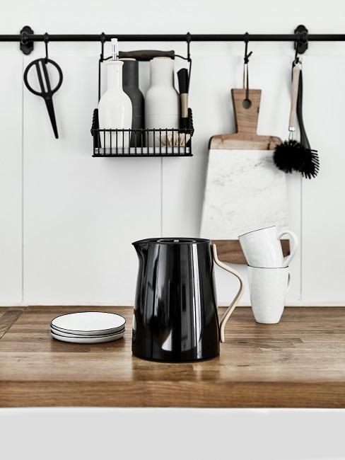 Isolierkanne auf der Küchenablage neben zwei Tassen, Untertellern, dahinter Küchenutensilien