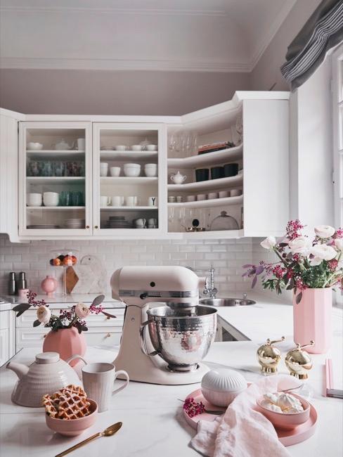 Cucina bianca con piastrelle, fiori e accessori