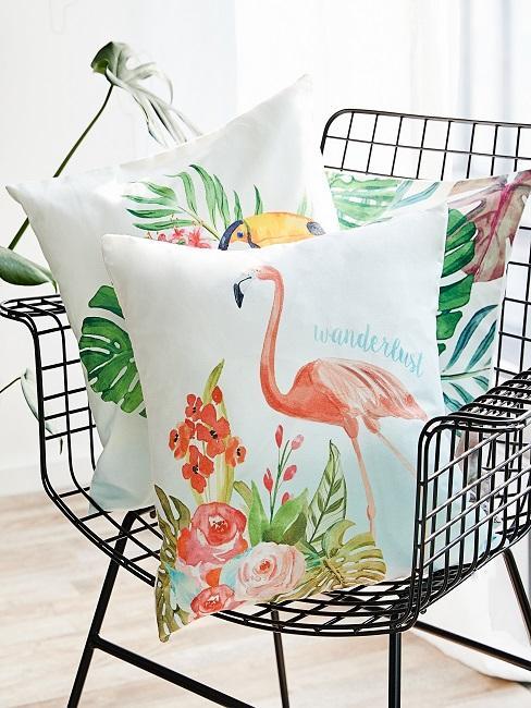 Kussen met flamingoprint op een zwarte stoel