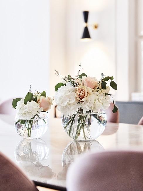 Zwei Glasvasen mit Rosen auf einem Esstisch