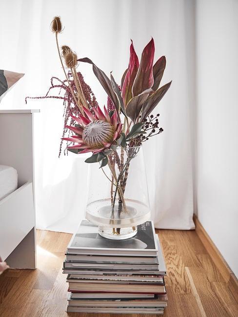 Hohe Vase auf Bücherturm mit roten Blumen