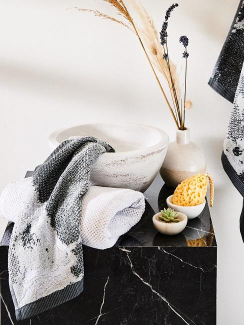 Bagno in marmo nero con asciugamani e prodotti da doccia