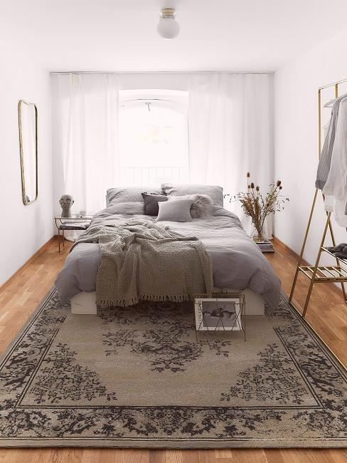 Bett in Grau, Strick-Plaid und ein Zeitschriftenhalter sowie eine große Vase als Deko
