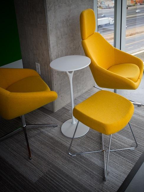 2 Stühle und ein Hocker in Gelb an einem kleinen weißen Tisch im 60er Style