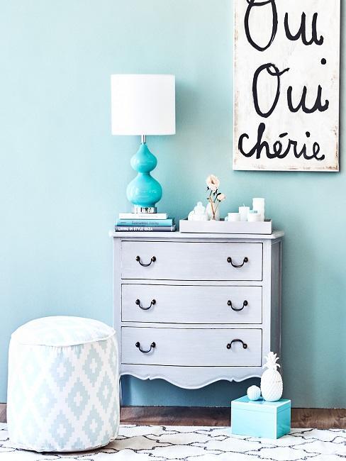 Blauer Flur mit weißer Kommode, Wandbild und Pouf mit Deko