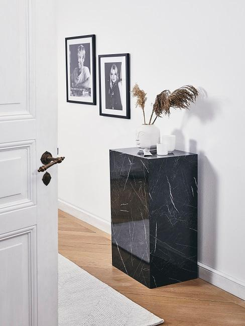 Beispiel minimalistisch Wohnen im Flur: EIne schwarze Konsole mit weißen Vasen neben zwei schwarz-weiß Bildern