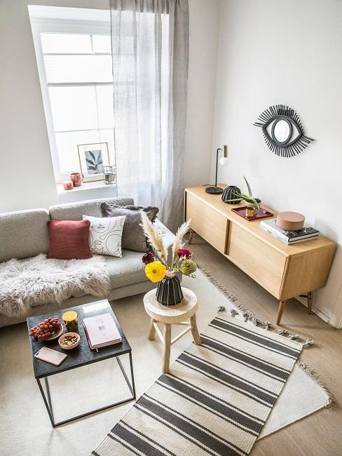Wohnraum von oben mit einer Couch, einem Couchisch und einem Sideboard aus hellem Holz.