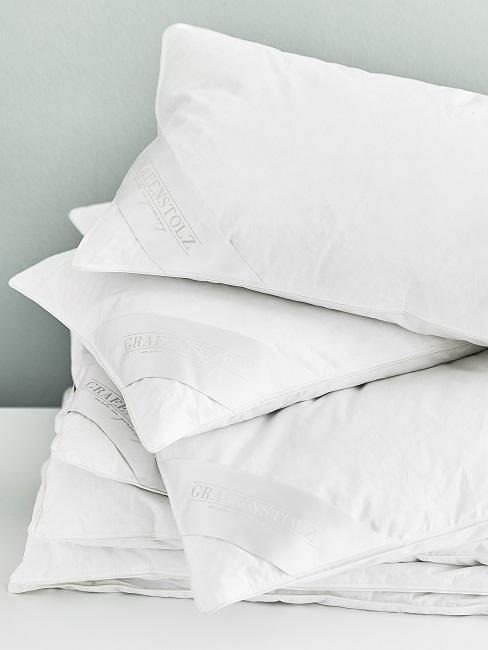 Ein Stapel an neuen Kissen auf einer weißen Ablage