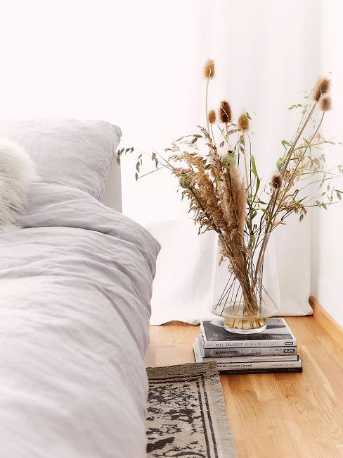Schlafzimmer mit einem minimalistischen Bett neben einem Bücherstapel mit einer Vase drauf mit Pampasgras Deko