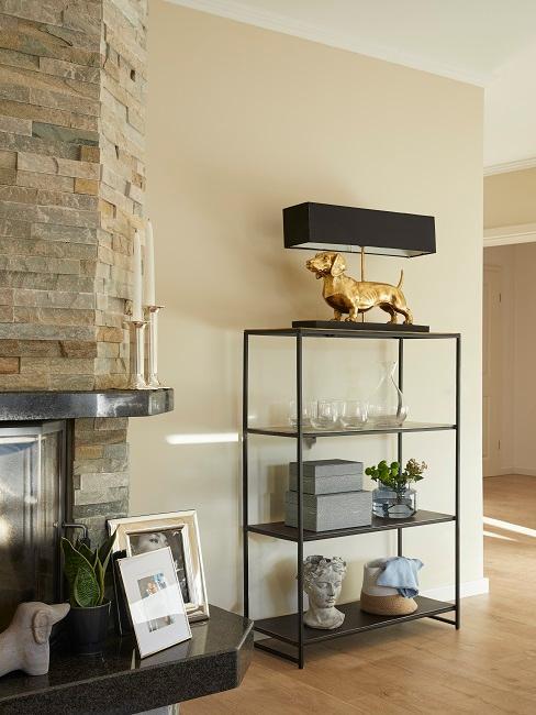 Wohnzimmer mit einem schwarzen Metallregal neben dem Kamin mit vielen Deko-Accessoires