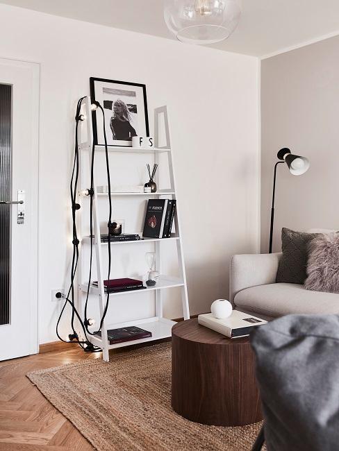 Wohnzimmer mit einem weißen Regal neben der Sofaecke mit Büchern, einem Wandbild und weiterer Deko