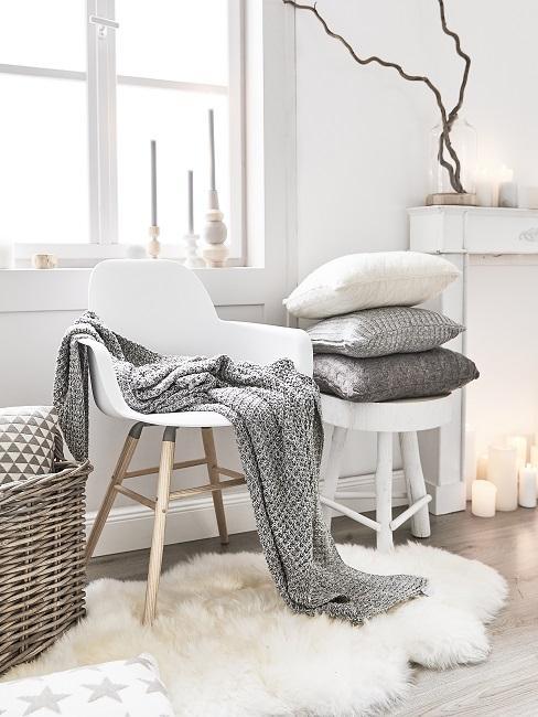Wohnzimmer mit einem Stuhl und einem Hocker in Weiß vor dem Fenster, darauf eie Decke und mehrere Kissen, auf dem Boden sorgt ein Schaffell Teppich für cozy Atmosphäre
