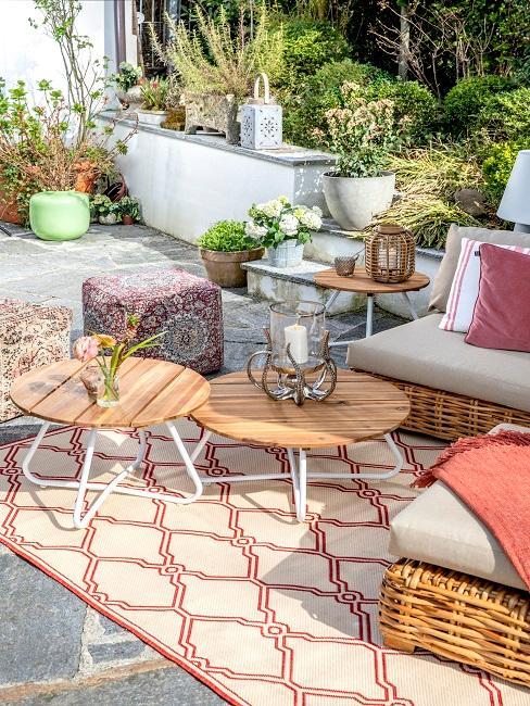 Terrasse mit einer Sitzecke mit Teppich, Sofa, vielen Poufs und mehreren Tischen als Luxus Möbel