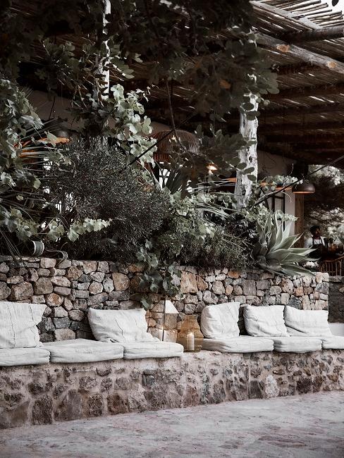 Stein Terrasse vom Luxus Garten mit einer Sitzbank mit vielen gemütlichen Kissen und Deko