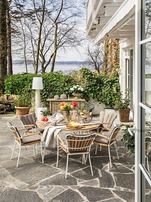 Luxus Terrasse mit einem gedeckten Tisch und Stühlen aus hochwertigem Holz