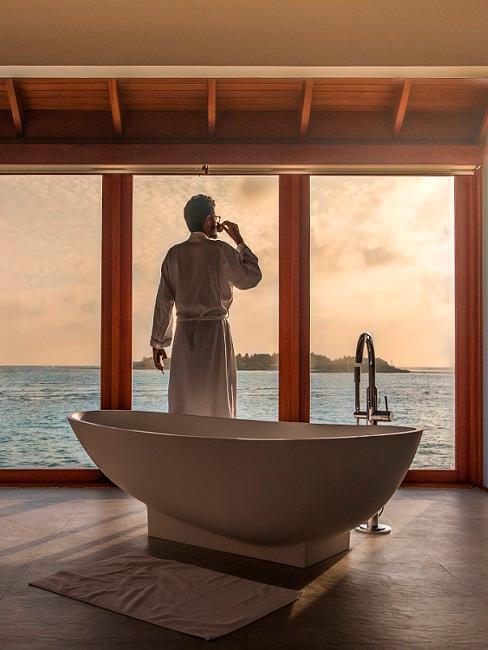 Mann steht vor Fenster und freistehender Badewanne
