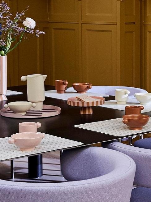Modern gedeckter Tisch neben violetten Stühlen