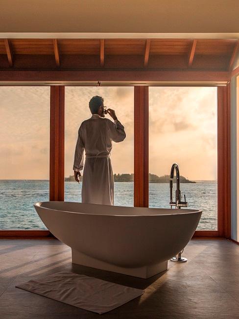 Mann hinter freistehender Badewanne vor Fenster