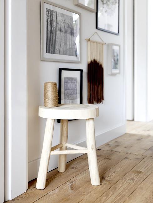Hocker aus hellem Holz in Flur mit Bilderwand