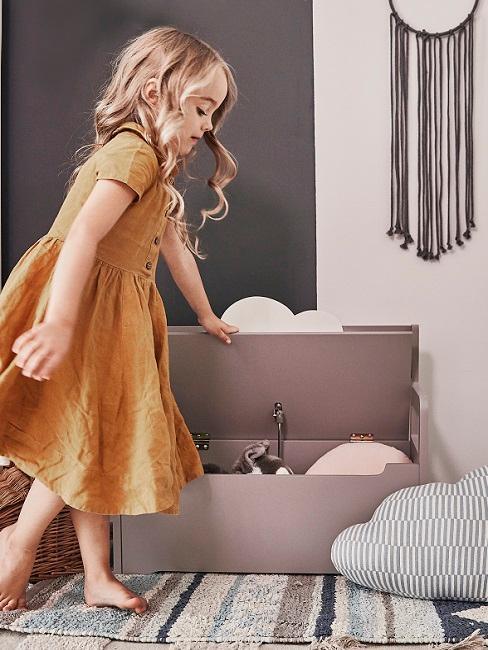 Mädchen räumt Spielzeug in Kiste