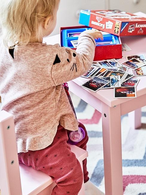 Kleines Mädchen spuet Memory am Tisch