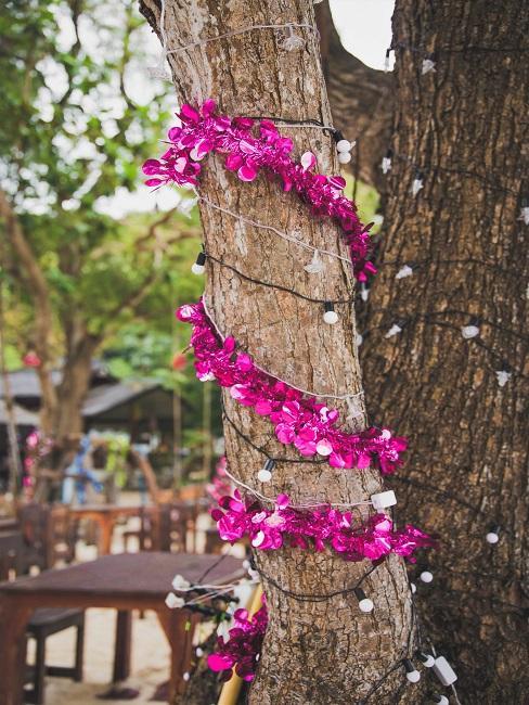Lila Blumedngirlande mit Lichterkette am Baum