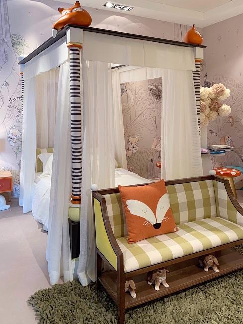 Kinderzimmer mit weißem Himmelbett, grünem Sofa und orangenen Kissen