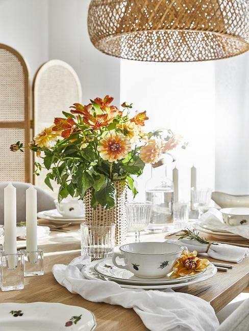Orangener Blumenstrauß in Glasvase auf Esstisch