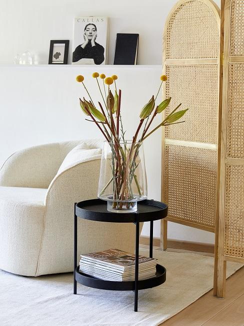 Schnittblumen in großer Glasvase auf schwarzem Beistelltisch
