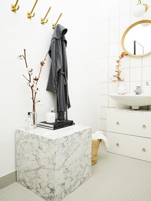 Weißes Bad mit Marmortisch, goldenen Wandhaken mit Bademattel und Wandspiegel