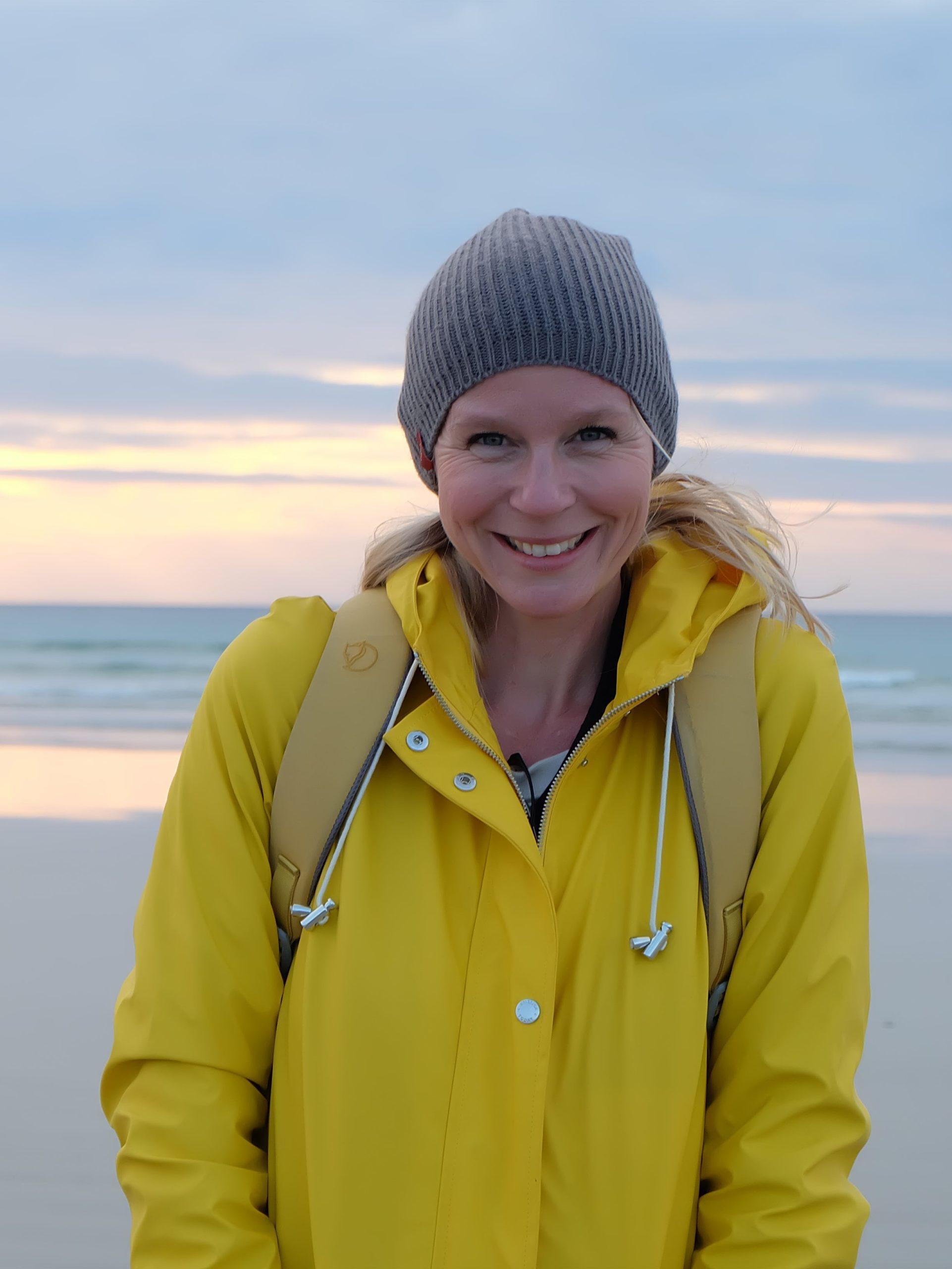 Frau in gelber Jacke am Strand
