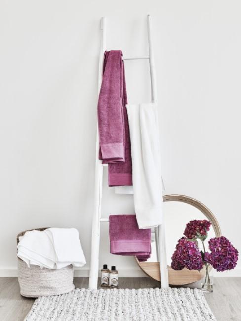 Lila Handtücher hängen auf Leiter in der Waschküche