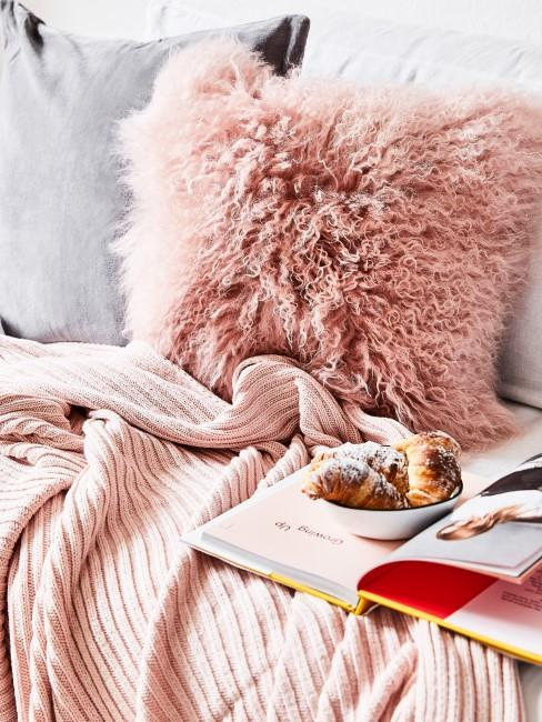 Rosa Kissen aus Fell liegt auf dem Sofa