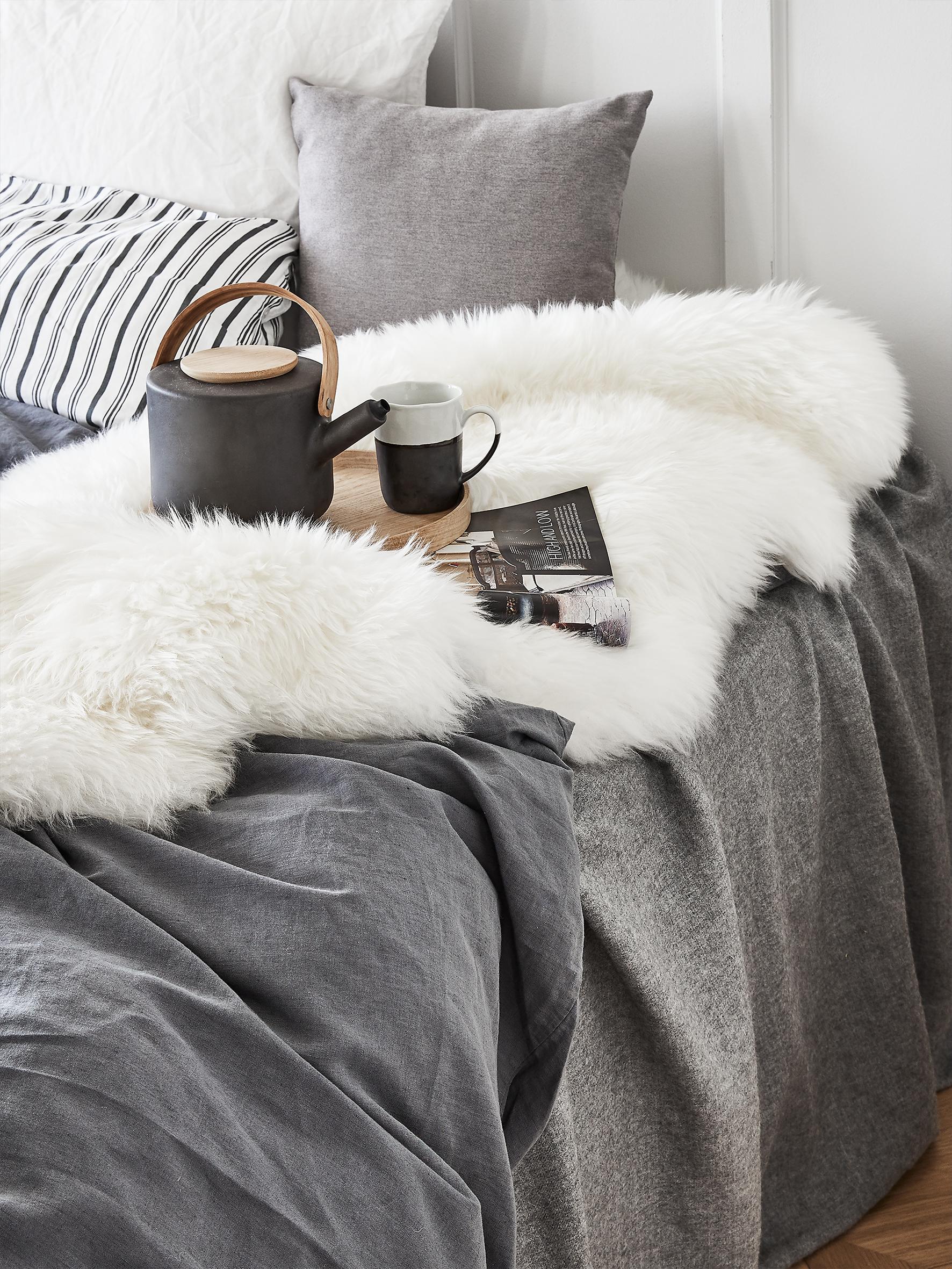 Fellteppiche in weiß auf dem Bett