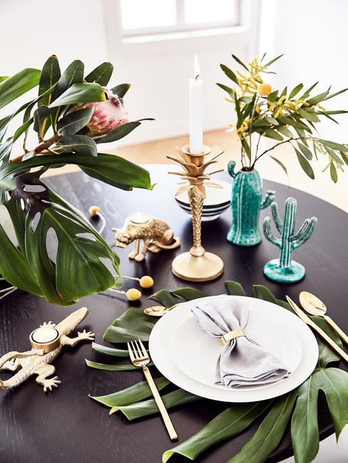 Mesa de comedor en negro con accesorios tripicales, cactus azul y plantas