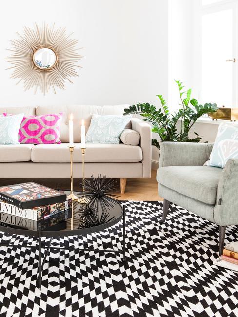 Salón co sofás beige y gris, alfombra de estampado negro y blanco geométrico y toques de color