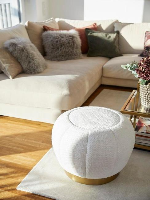 Salón con pouf blanco en primer plano y al fondo un sofá esquinero