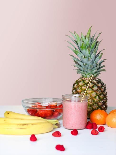 Plátanos, fresas, frambuesas, mandarinas y piña detrás de un vaso con batido de frutas