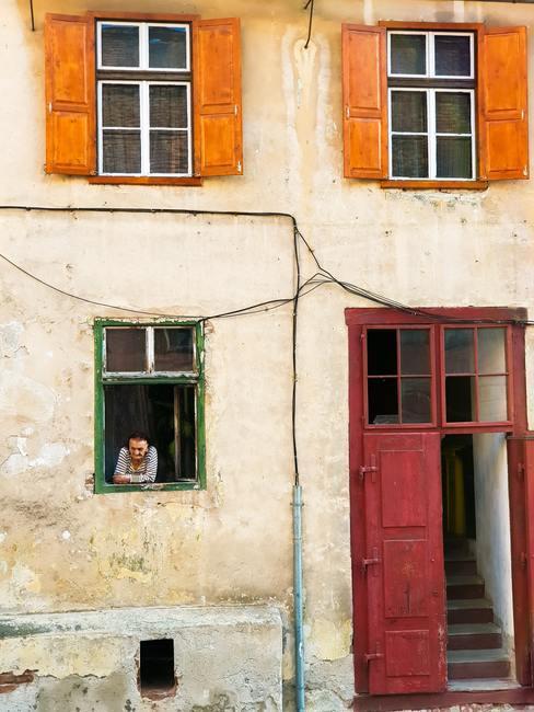 Casa de pueblo con persona apoyada en la ventana