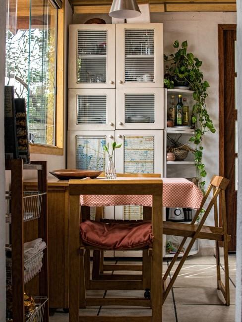 Pequeña cocina rústica de madera con mantel de cuadros sobre la mesa