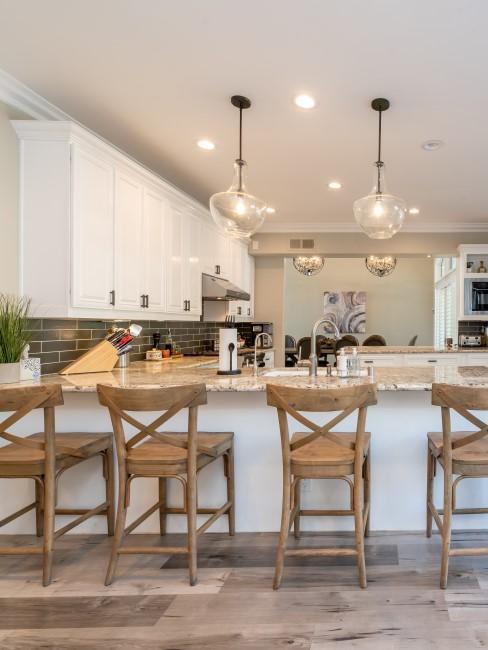 Cocina amplia con taburetes de madera y respaldo y dos lámparas colgantes